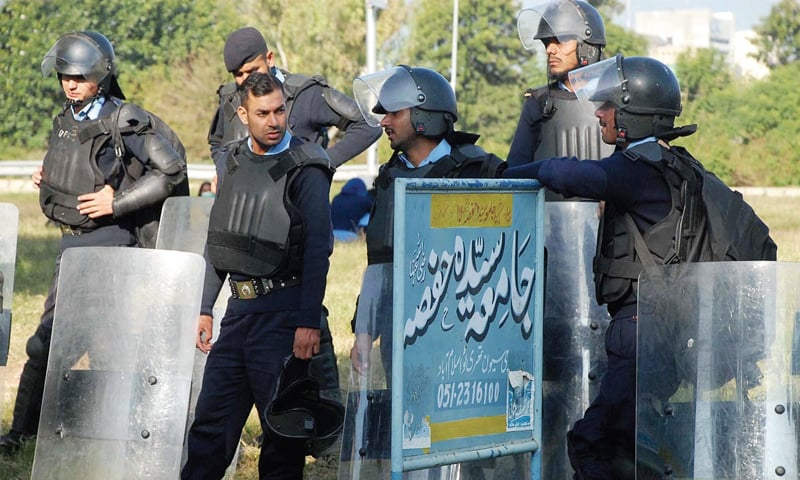 Policemen stand alert outside Jamia Hafsa in Islamabad on Friday. — Online