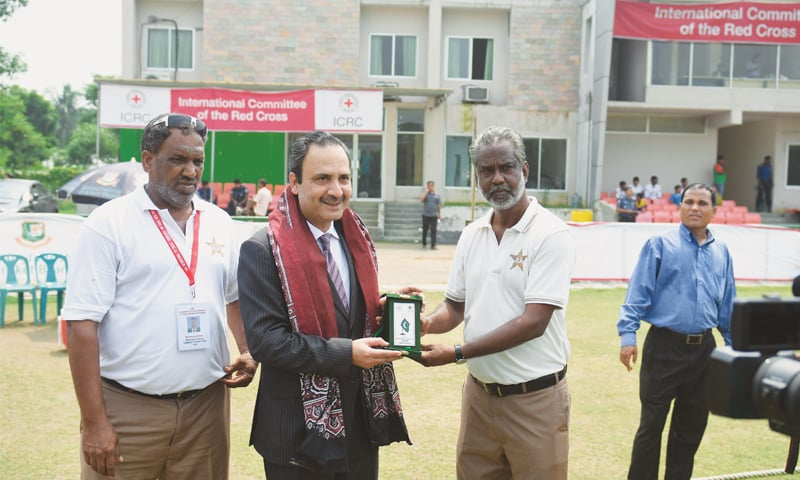 Mohammad Nizam (left) and Amiruddin Ansari (right) presenting a memento to the Pakistan High Commissioner  during the ICRC International T20 Cricket tournament in Bangladesh