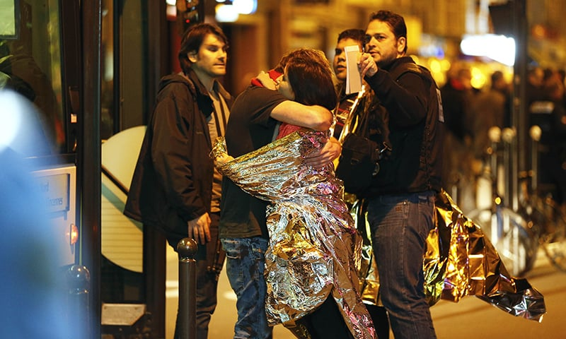 People hug each other before being evacuated by bus, near the Bataclan concert hall in central Paris, on November 14, 2015.  —AFP