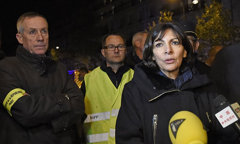 Paris mayor Anne Hidalgo (R) addresses the media as Paris prosecutor Francois Molins (L) looks on, near the Bataclan concert hall in central Paris, early on November 14, 2015. —AFP