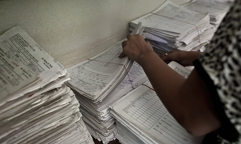 A worker sifts through paperwork at the Akanksha Clinic in Anand, India. — AP