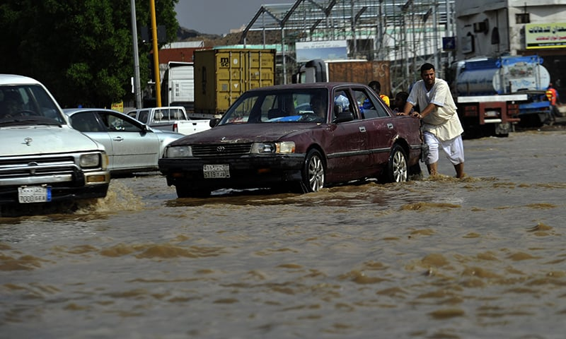 A Saudi man pushes his car in flooded water following heavy rainfall in the Saudi Arabian port city of Jeddah. — AFP