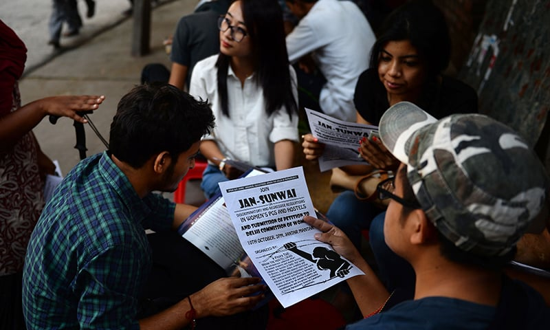 Indian students hold pamphlets as they listen to student activist Shriya Subhashini (unseen) outside Delhi University's North Campus in New Delhi. —AFP