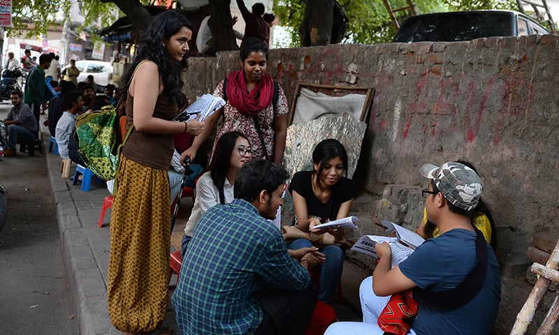 Indian student activists Shambhawi Vikram (L) and Shriya Subhashini (C) speak to fellow students as they distribute leaflets outside Delhi University's North Campus in New Delhi. —AFP