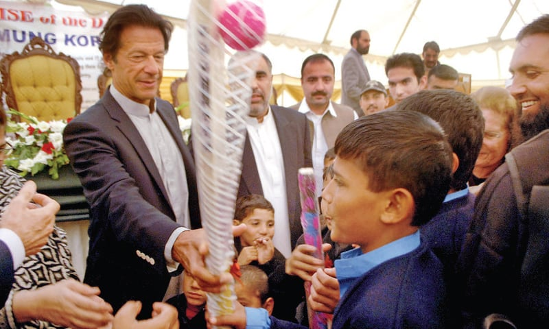 PTI chairman Imran Khan hands over a gift to a boy at the inaugural ceremony of a model institute for street children in Peshawar on Friday. — White Star