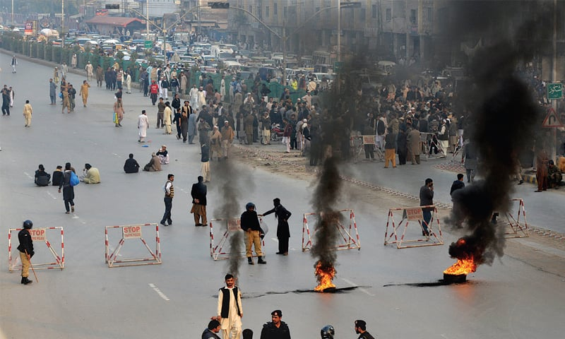 ANP activists and relatives burn tyres to block main GT Road, Peshawar, on Friday against the killing of a local party leader. —Photo by Shahbaz Butt