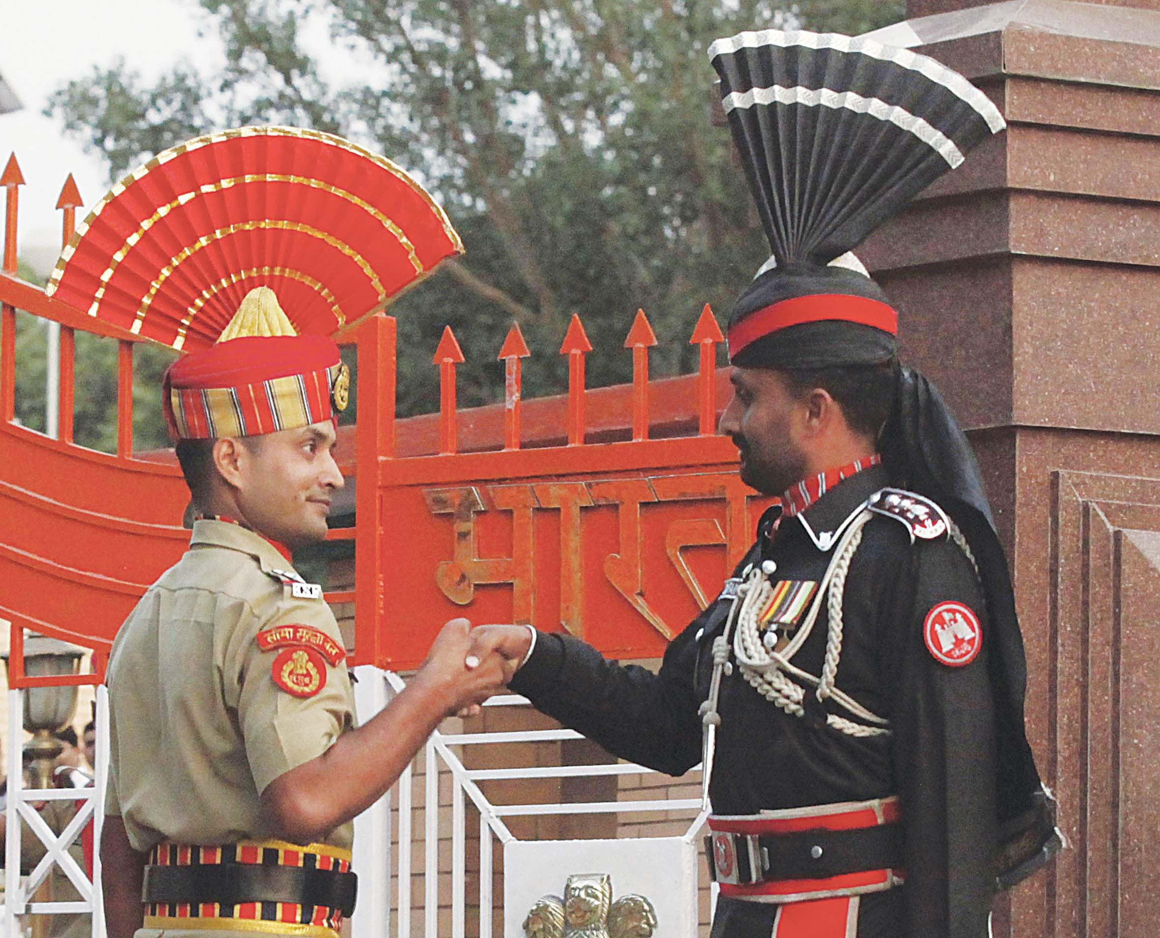 Pakistani and Indian border security personnel shake hands during the daily parade at the Wagah border. 	— Reuters