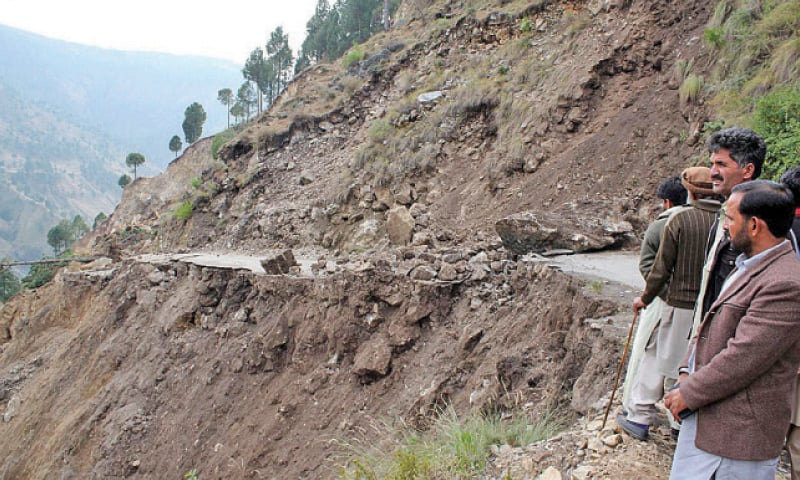 People stand close to a road that was damaged in a landslide near Abbottabad on Sunday. —Online