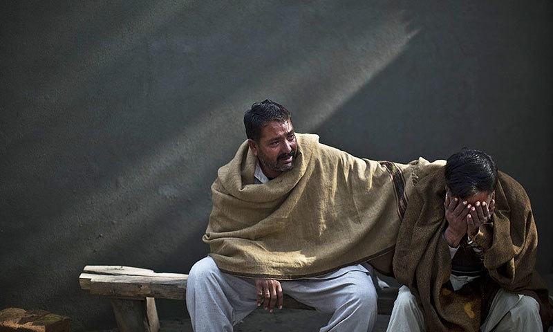 Family of a student, Zoubair Latif, 17, who was killed in a suicide bombing on January 2014, wait at a hospital in Rawalpindi to take the body for burial. —AP