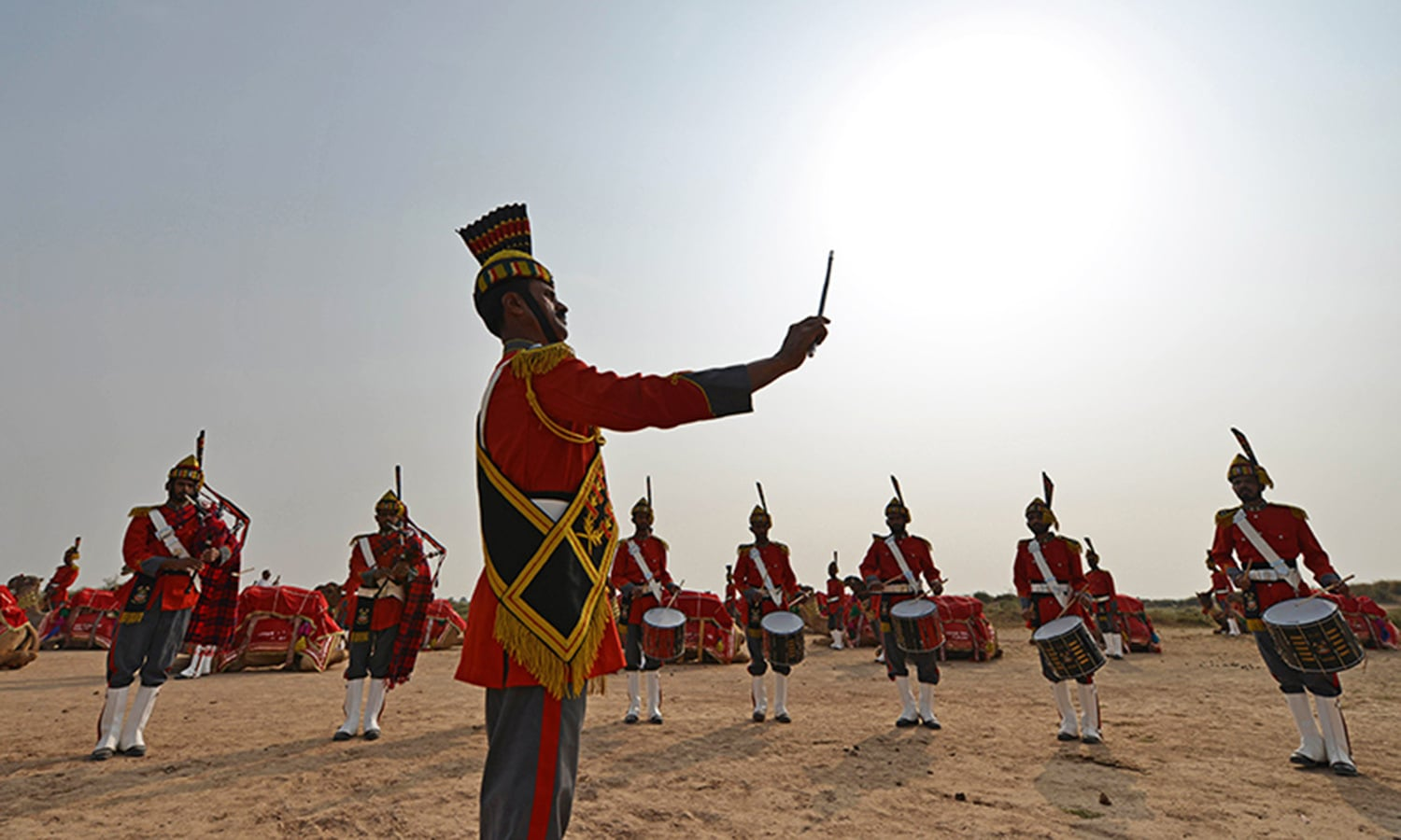 In this photograph taken on November 13, 2015, Band Major of Pakistan Desert Rangers, Muhammad Iqbal (C) conducts his team members before they mount on camels for a march in Moj Garh, some 100 kilometres east of Bahawalpur in Punjab Province. —AFP