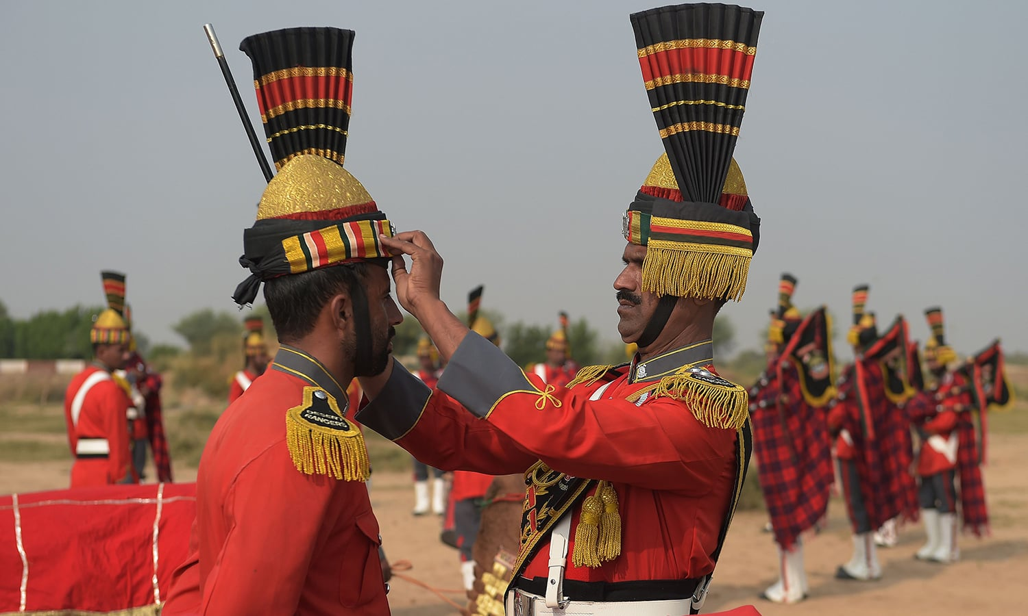 In this photograph taken on November 13, 2015, Band Major of Pakistan Desert Rangers, Muhammad Iqbal (R) adjusts a traditional hat of a team member before they mount camels for a march in Moj Garh, some 100 kilometres east of Bahawalpur in Punjab province. —AFP