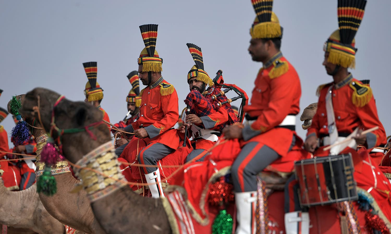 In this photograph taken on November 13, 2015, band members of Pakistan Desert Rangers sit on their camels as they perform during a march in Moj Garh, some 100 kilometres east of Bahawalpur in Punjab province. —AFP