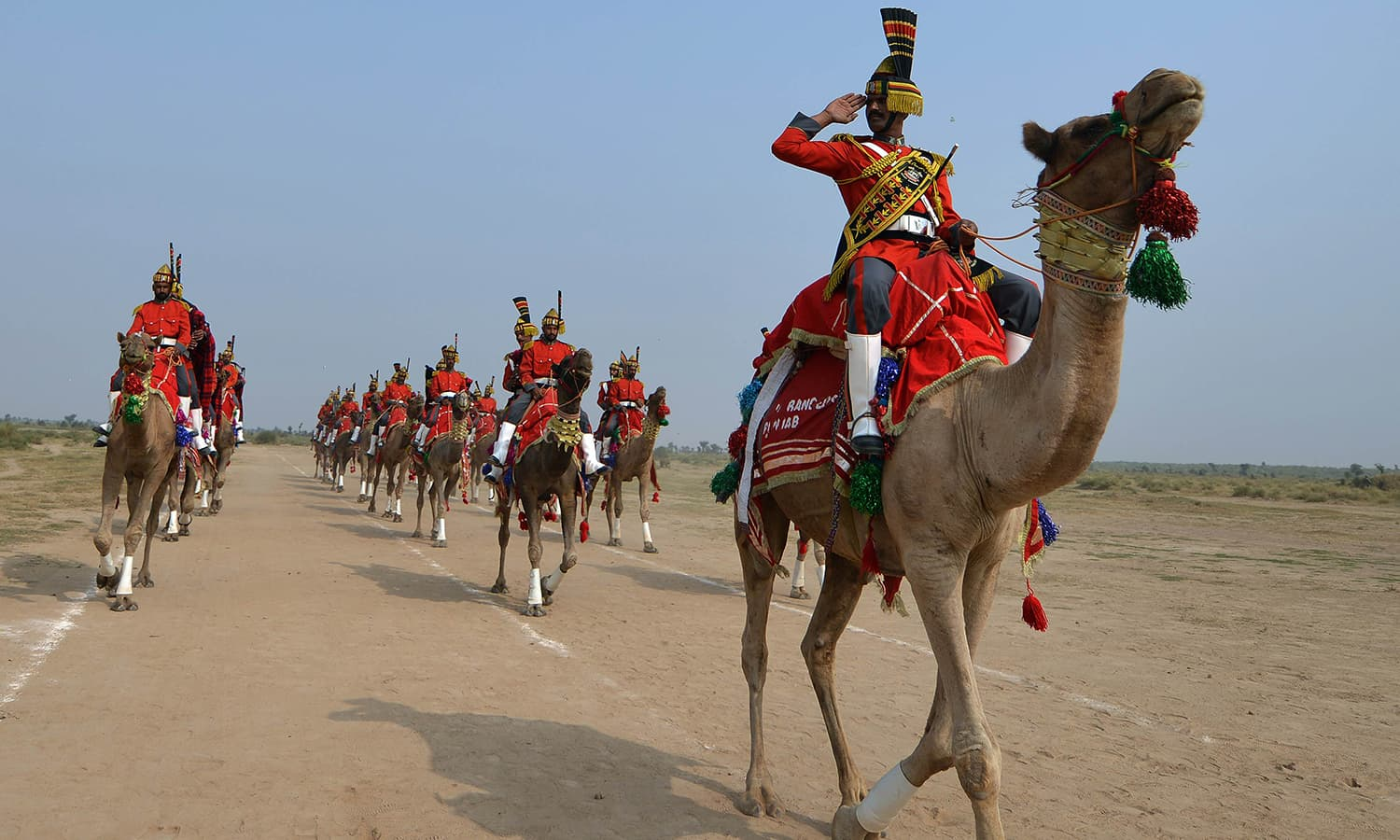 In this photograph taken on November 13, 2015, Band Major of Pakistan Desert Rangers, Muhammad Iqbal (R) salutrs as he conducts team members mounted on camels during a march in Moj Garh, some 100 kilometres east of Bahawalpur in Punjab province. —AFP
