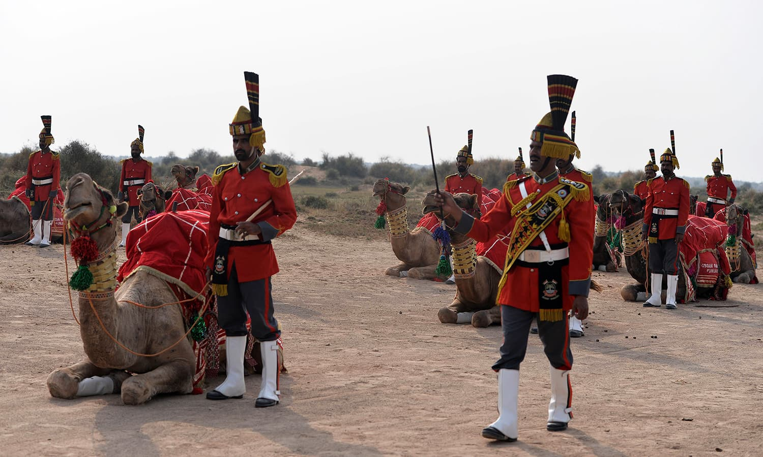 In this photograph taken on November 13, 2015, Band Major of Pakistan Desert Rangers, Muhammad Iqbal (R) instructs team members before they mount on camels for the march in Moj Garh, some 100 kilometres east of Bahawalpur in Punjab province. —AFP
