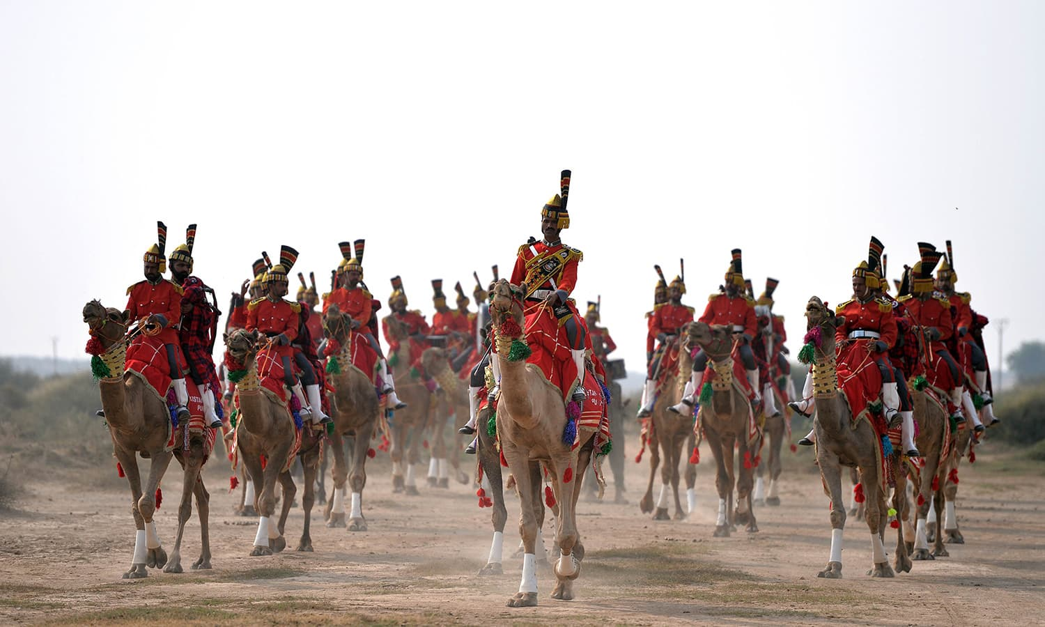 In this photograph taken on November 13, 2015, Band Major of Pakistan Desert Rangers, Muhammad Iqbal (C) leads while conducting team members mounted on camels during the march in Moj Garh, 100 kilometres east of the city of Bahawalpur in Punjab province. —AFP