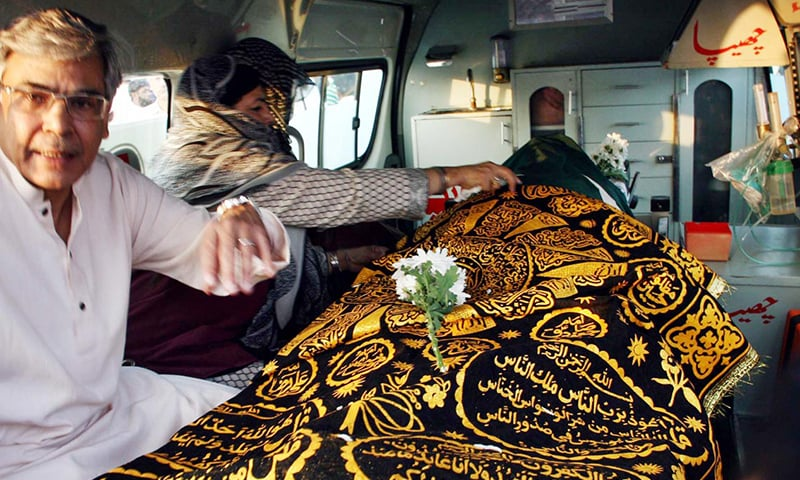 Wife of Jamiluddin Aali seen sitting with his coffin in an ambulance after the offering of his funeral prayer at Masjid-i-Tooba. ─ Online