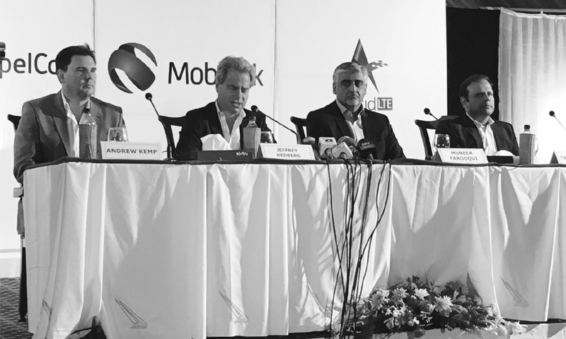 The Mobilink and Warid CEOs announcing the merger at a press conference in Lahore last year. —File