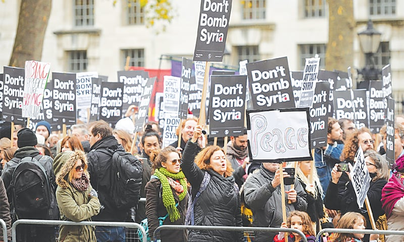 LONDON: Protesters hold a demonstration, organised by Stop the War Coalition, near the houses of parliament against the proposed bombing of the militant Islamic State (IS) group in Syria.—AP