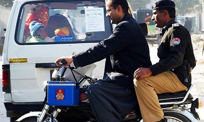 ایک پولیس اہلکار پولیو ورکر کے ہمراہ انسدادِ پولیو مہم کے دوران سیکیورٹی پر مامور ہے—۔فائل فوٹو/ آن لائن
