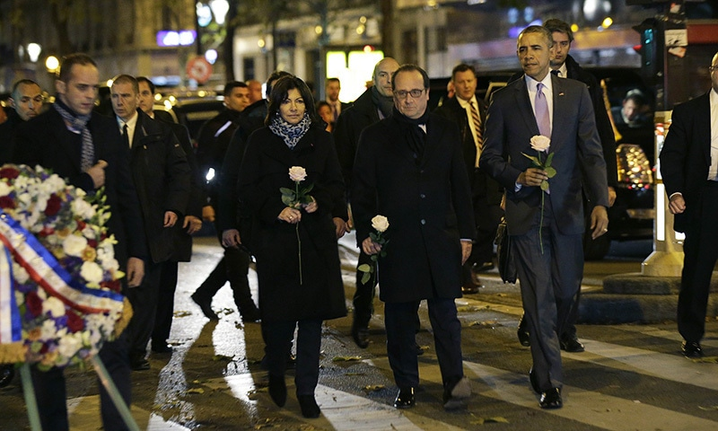 US President Barack Obama (R), French President Francois Hollande (C) and Paris Mayor Anne Hildago arrive to pay their respects at the memorial outside the Bataclan in Paris, on November 30, 2015, after Obama arrived in the French capital to attend the World Climate Change Conference 2015 (COP21). —AFP