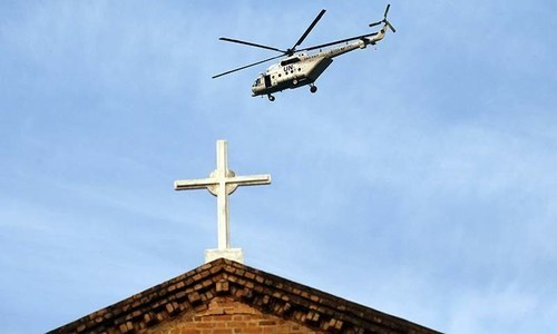 A UN peacekeeping helicopter flies over Bangui's cathedral prior to the arrival of Pope Francis to open a holy door. ─ AP