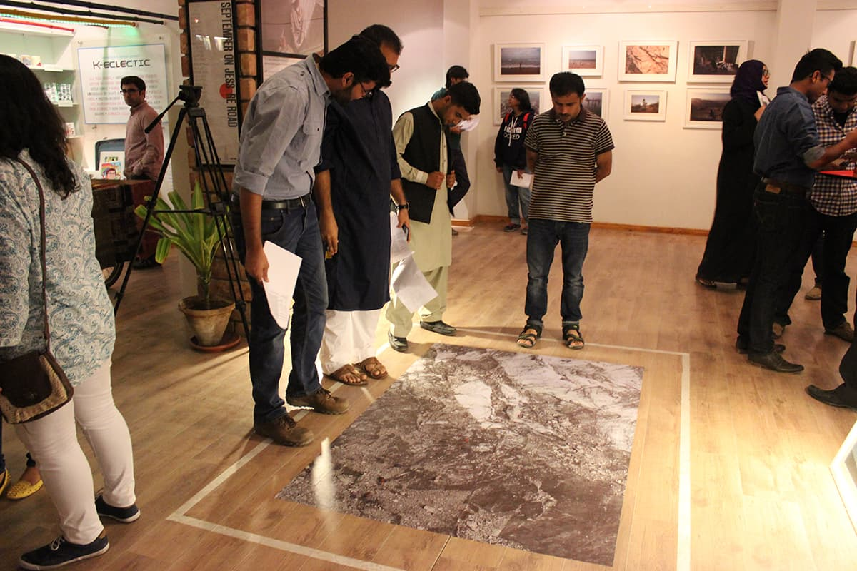 Attendees look at the floor installation of Danial's photo. — Photo by Ibtisam Khanzada