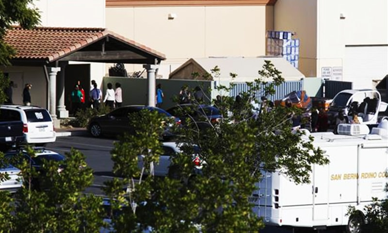 People evacuated from the Inland Regional Center walk from buses into The Rock Church and World Outreach Center. — AFP