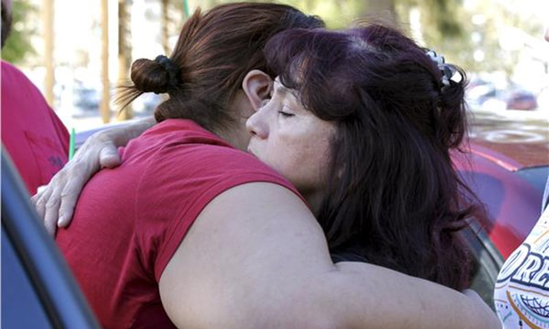 Teresa Hernandez (R) hugs Monique Gutierrez at the Rudy Hernandez Community Center as they wait for a relative who was not injured after the shooting rampage. — Reuters