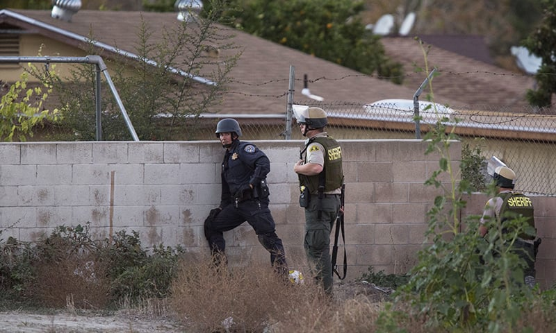 Law enforcement officers search for a possible suspect following a shootout with suspects of a mass shooting at the Inland Regional Center by multiple gunmen on December 2, 2015 in San Bernardino, California. —AFP