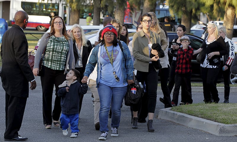Survivors of the Inland Regional Center where gunmen shot and killed 14 people and injured another 14, are escorted off buses to meet relatives at the Rudy Hernandez Community Center in San Bernardino, California December 2, 2015.—Reuters