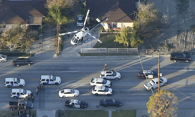 A police helicopter flies over emergency vehicles during a manhunt following the mass shooting in San Bernardino, California. —Reuters