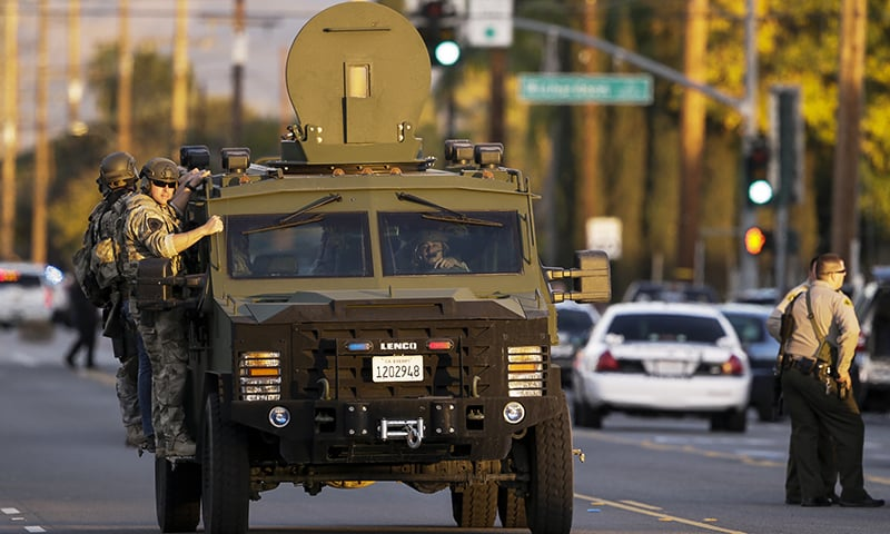 Authorities search an area near where police stopped a suspected vehicle in San Bernardino. —AP