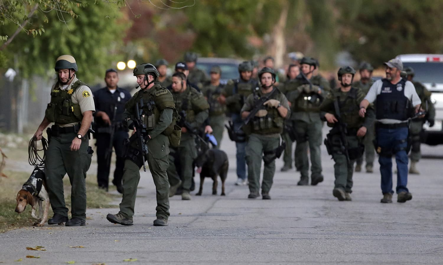 Authorities search for a suspect following the shooting. ─ AP