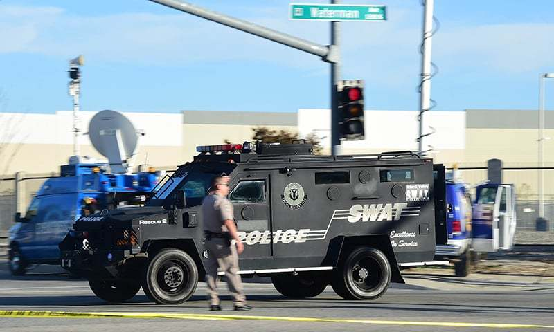 A SWAT police vehicle speeds past an officer on patrol. ─ AFP