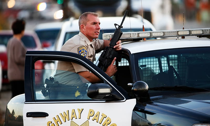 A California Highway Patrol officer stands with his weapon as authorities pursued the suspects in a shooting that occurred at the Inland Regional Center. -AFP