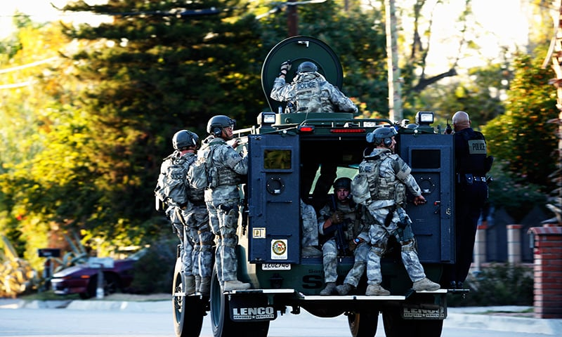 SWAT officers enter an area where suspects were believed to be after the shooting at the Inland Regional Center. -AFP