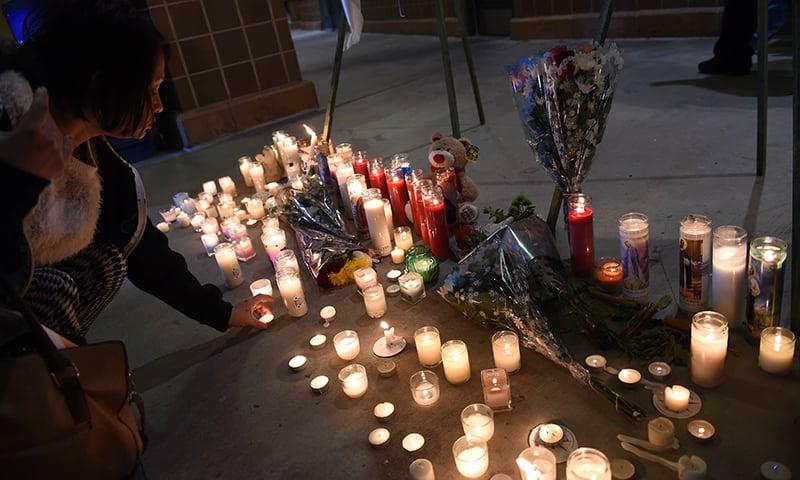 People leave candles at a memorial at the San Manuel Stadium in San Bernardino, California. — AFP