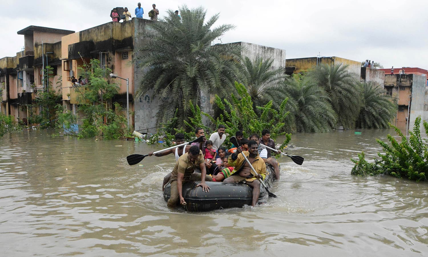 Indian rescue personnel and police officials paddle an inflatable boat through floodwaters as they evacuate residents in Chennai on December 2, 2015. — AFP