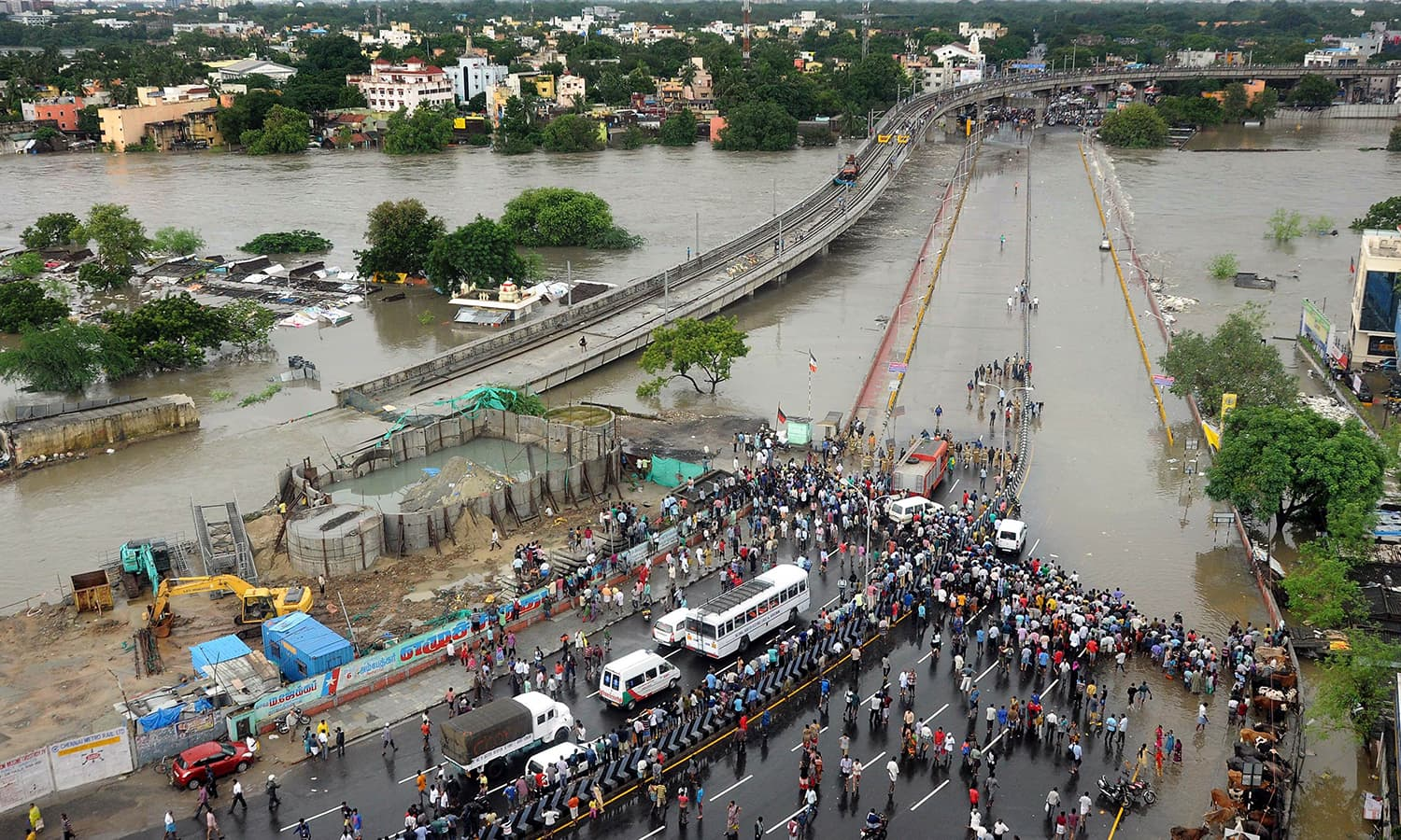 Indian bystanders and travellers gather as floodwaters lap at the end of a highway in Chennai on December 2, 2015. — AFP