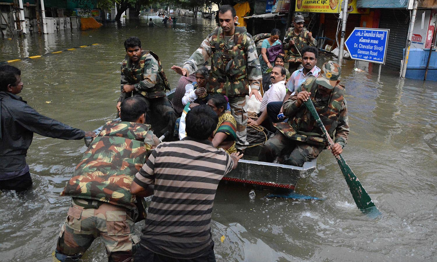 Indian army personnel use a boat to rescue residents from floodwaters in Chennai on December 3, 2015.  Thousands of rescuers raced to evacuate residents from deadly flooding, as India's Prime Minister Narendra Modi went to the southern state of Tamil Nadu to survey the devastation. — AFP