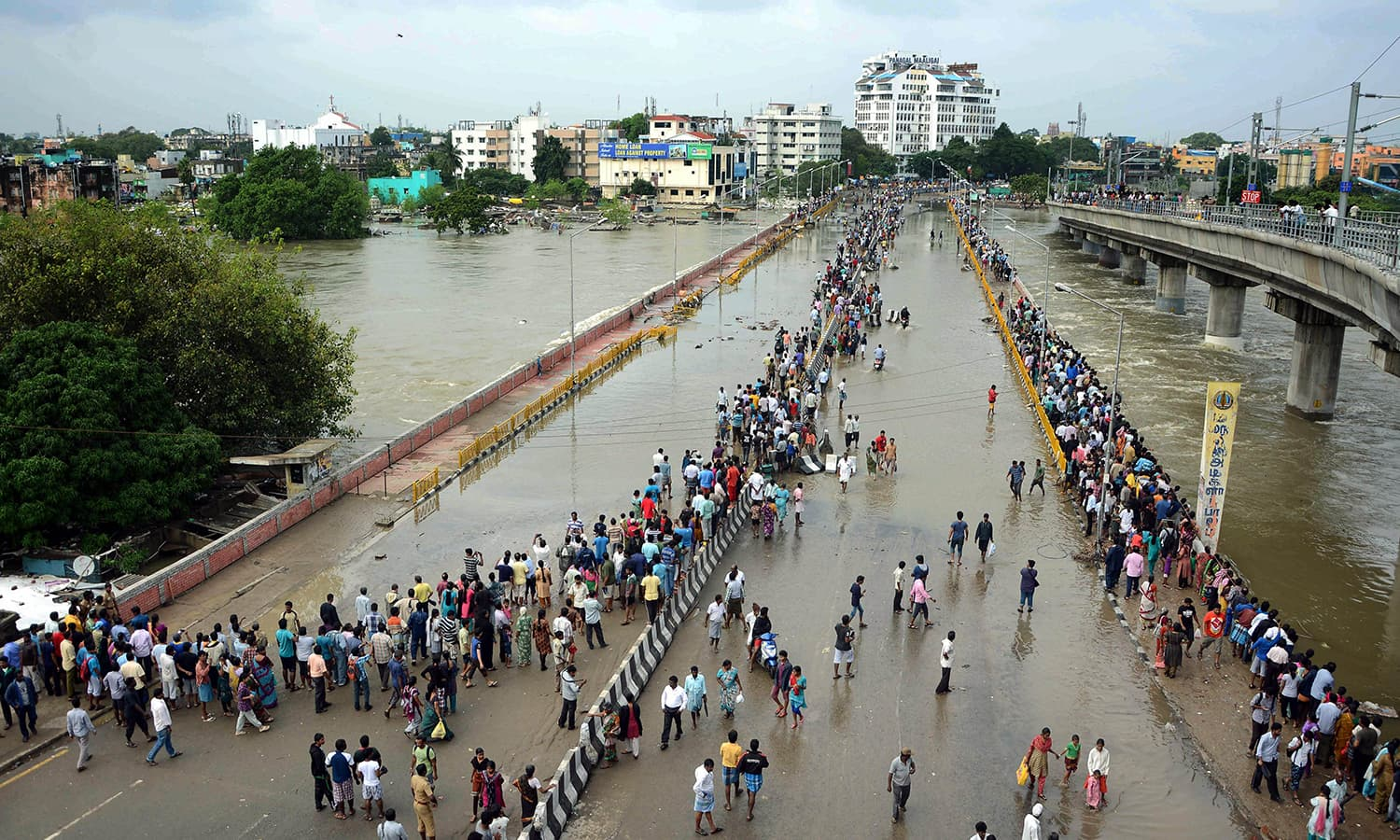 This general view shows Indian residents as they look at floodwaters on a major highway in Chennai on December 3, 2015.  — AFP