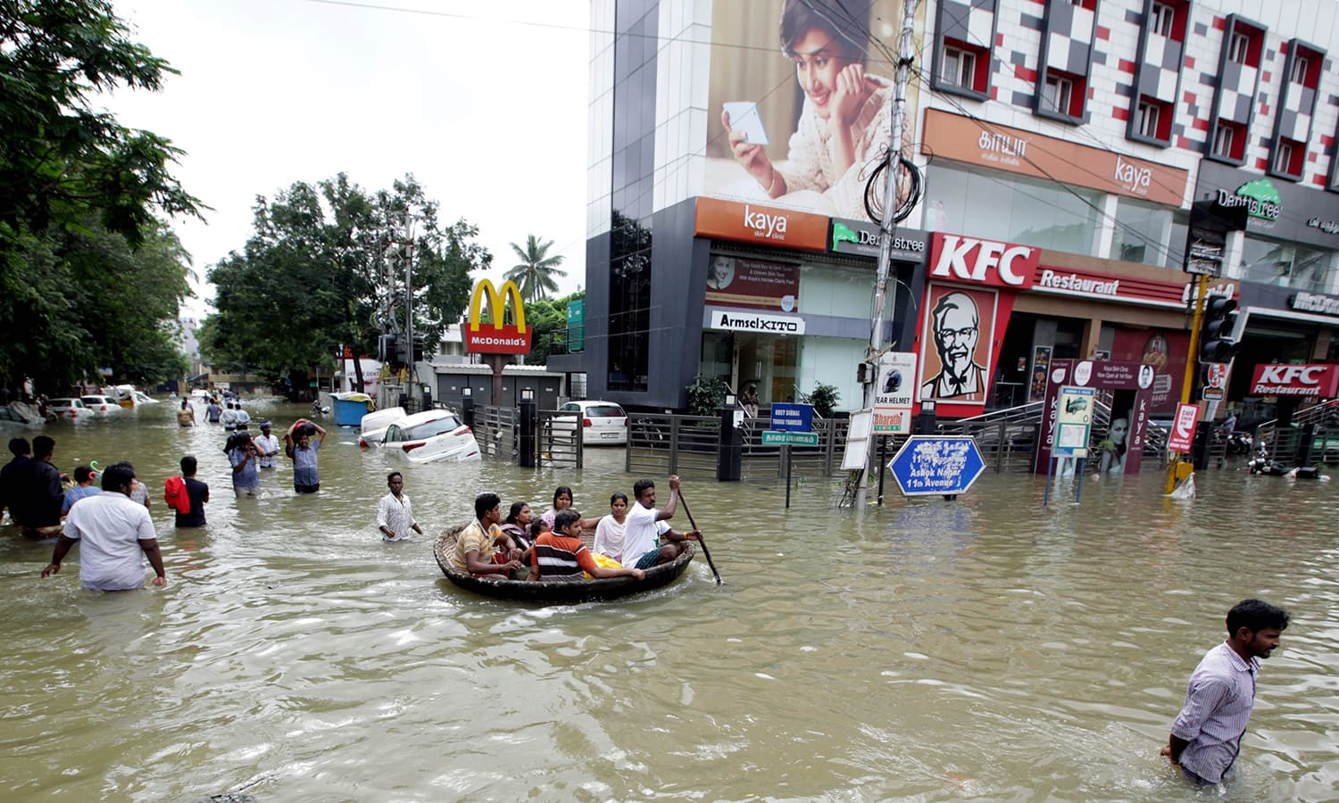 Indian residents make their way through floodwaters in Chennai on December 3, 2015. — AFP