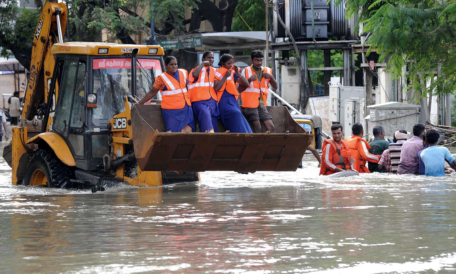 Indian rescue workers travel in the bucket of a bulldozer as they navigate through floodwaters in Chennai on December 3, 2015. — AFP