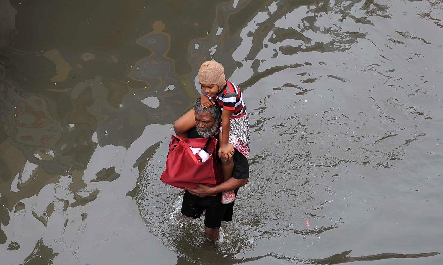 An elderly Indian man carries a child as he walks through floodwaters in Chennai on December 3, 2015. — AFP