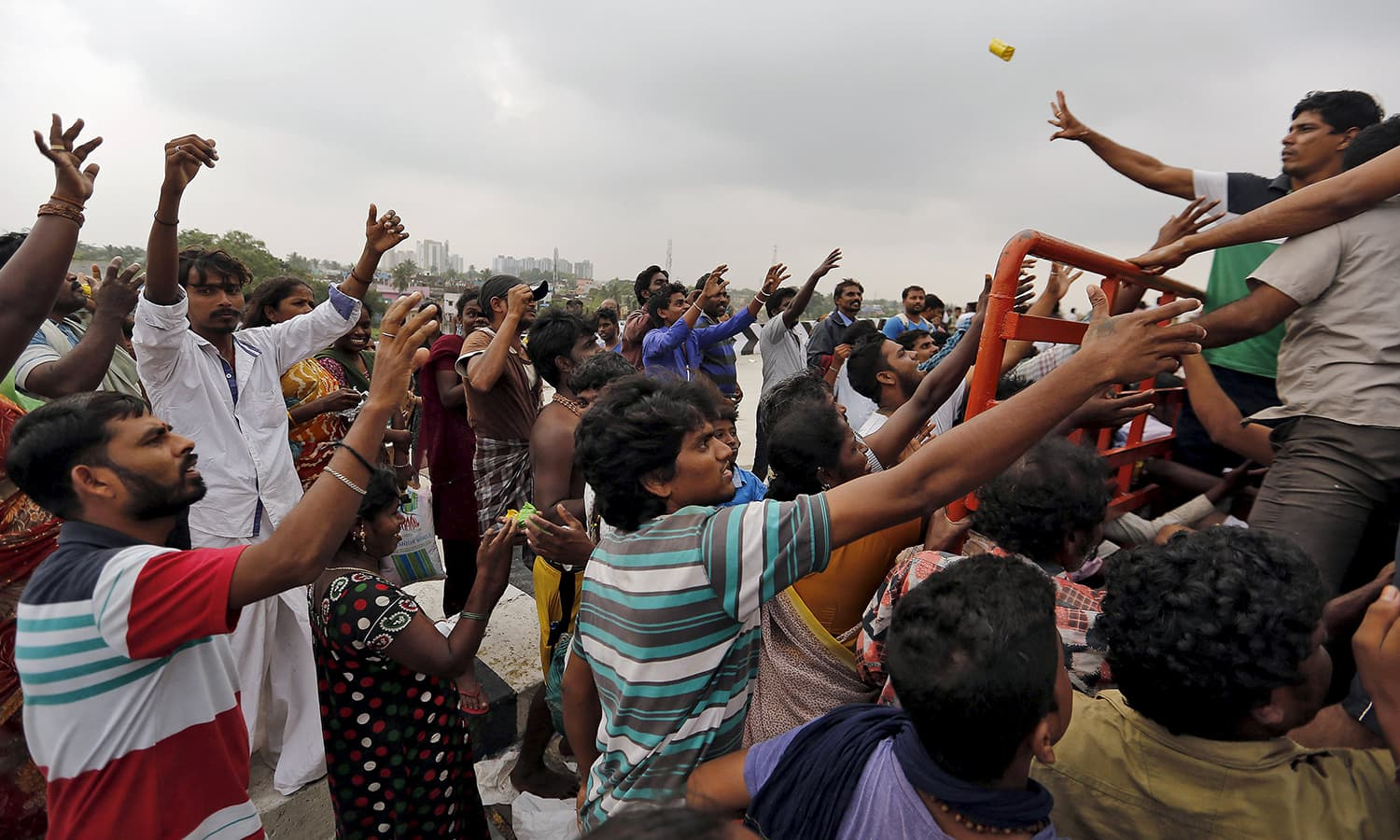 Displaced residents try to grab free food distributed by volunteers in the flood-affected areas of Chennai, India, December 3, 2015. — Reuetrs