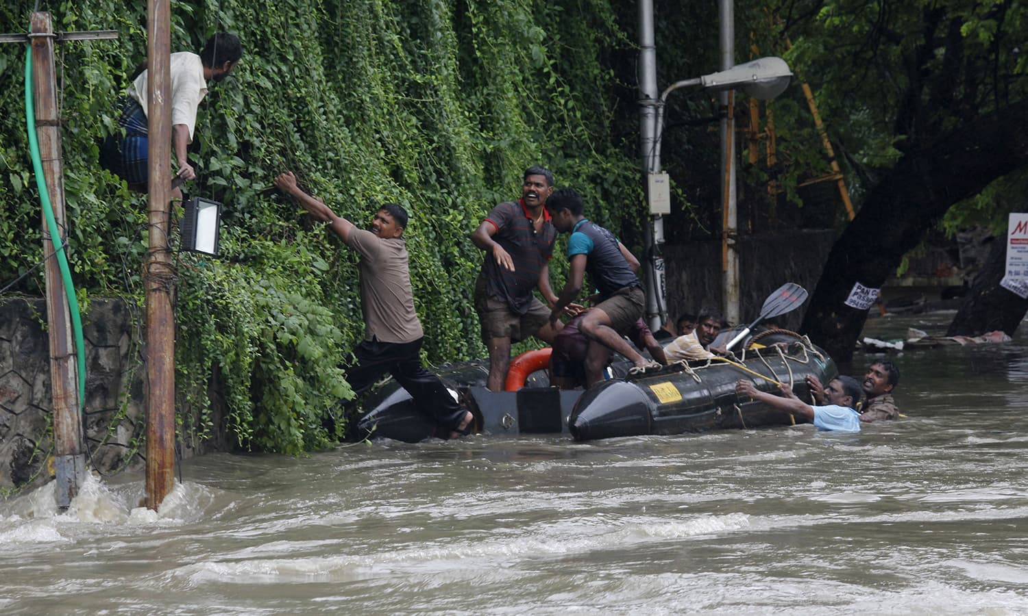Rescuers try to evacuate a man stranded in the floods by an over-flowing Adyar River in Chennai, Tamil Nadu, India, Wednesday, Dec. 2, 2015. — AP