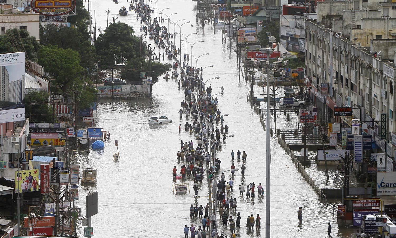 People walk through a flooded street in Chennai, India, Thursday, Dec. 3, 2015. — AP
