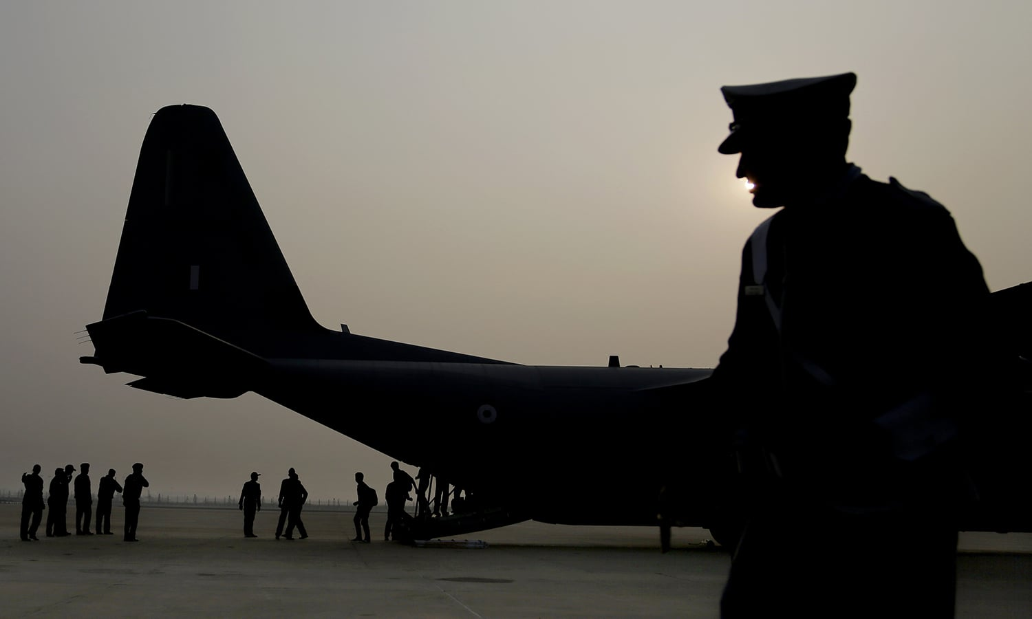 An Indian Air Force personnel is silhouetted as people who were stranded in Chennai due to floods deplane in New Delhi after being evacuated by the air force Thursday, Dec. 3, 2015. — AP