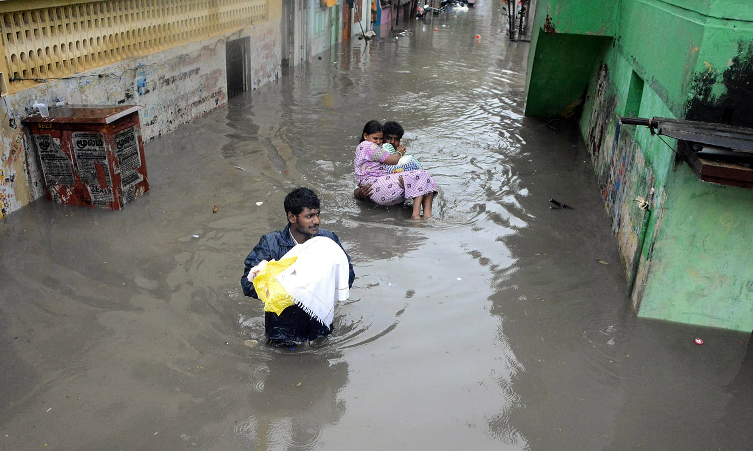 Indian residents walk through floodwaters in Chennai on December 2, 2015.  — AFP
