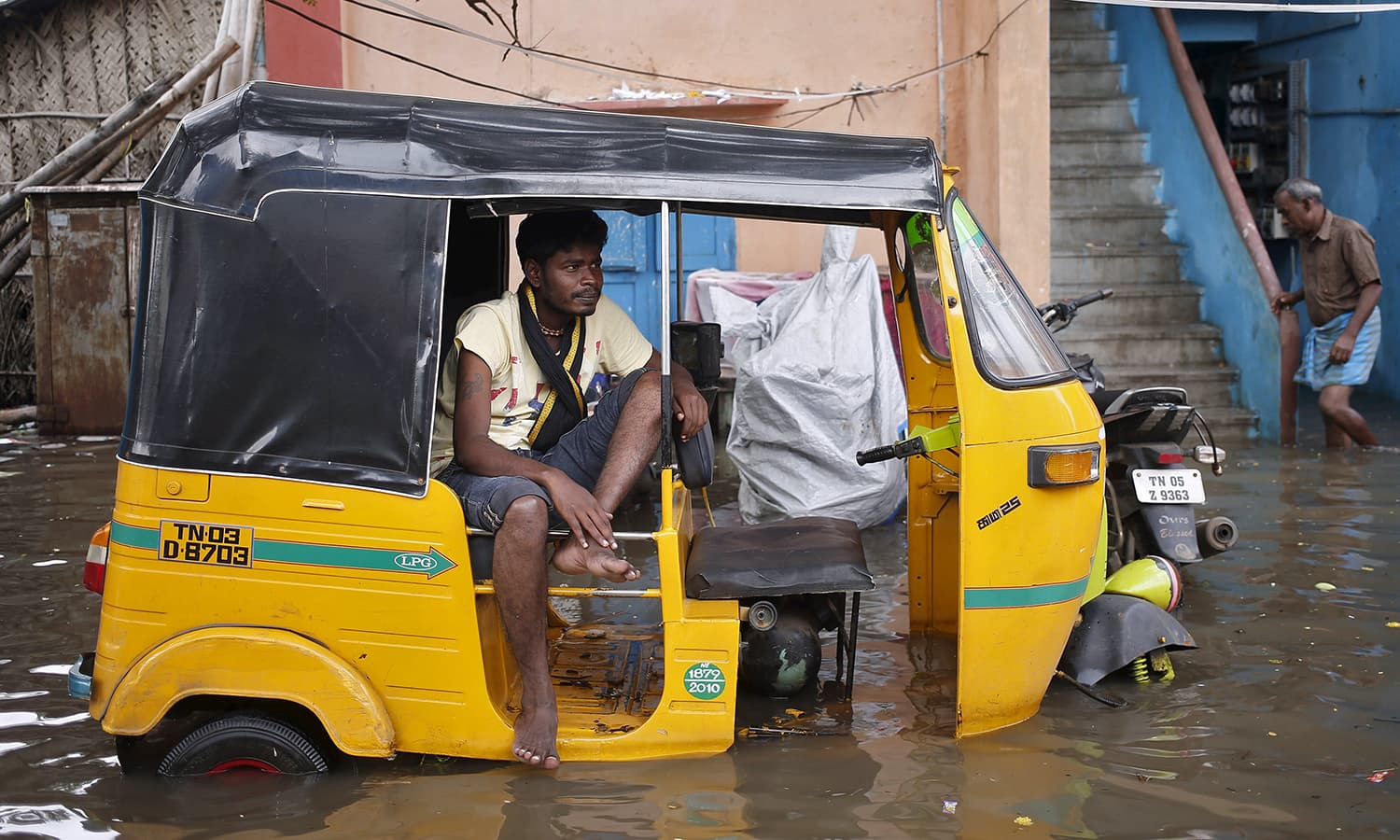 A man sits in an auto-rickshaw in a flooded area in Chennai, India, December 3, 2015. — Reuters